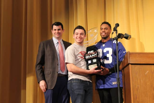 Mahopac High School senior Charlie Burt receives the Heart of a Giant award from Giants' running back Rashad Jennings and Hospital for Special Surgery's Dr. Sam Taylor.
