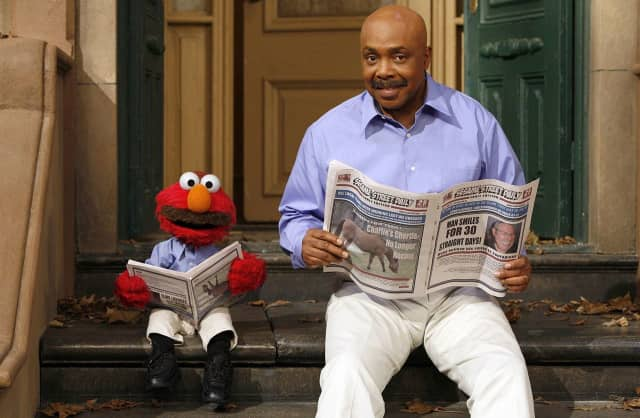 "Roscoe Orman, as Gordon, reads with Elmo on ""Sesame Street."""