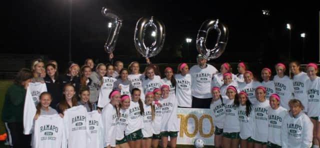 The Ramapo High School girls soccer team celebrate a milestone win with head coach Paul Heenehan.