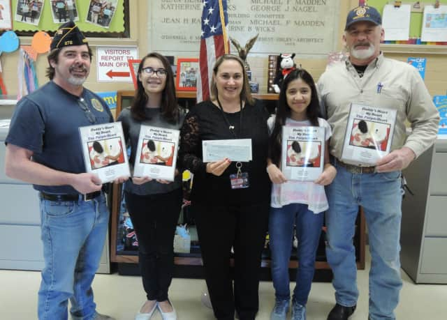 Commander Fred Reiman and Steven Minch of the Norwood American Legion Post 272 purchased copies of a student-written book on PTSD to donate to Norwood school children.