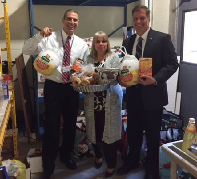 Mahopac Middle School principal Vincent DiGrandi, assistant principal Anna O'Connor and Carmel Town Councilman Frank Lombardi show off some of the food items that were gathered for those in need this Thanksgiving.
