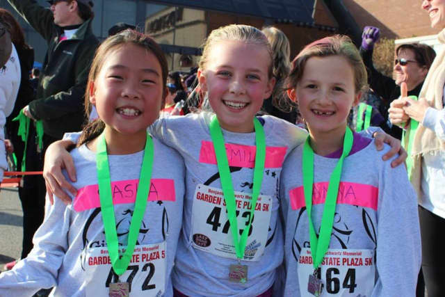 Young runners and their medals after finishing the Girls on the Run 5K at the Garden State Plaza.
