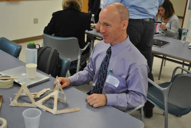 Putnam Valley math teacher Joe Mahoney attempts to build a structure from Popsicle sticks and tape that can support 12 pounds.