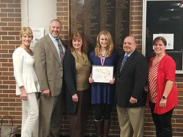 Leah Feniger with her parents and school officials after being honored as a student of distinction.