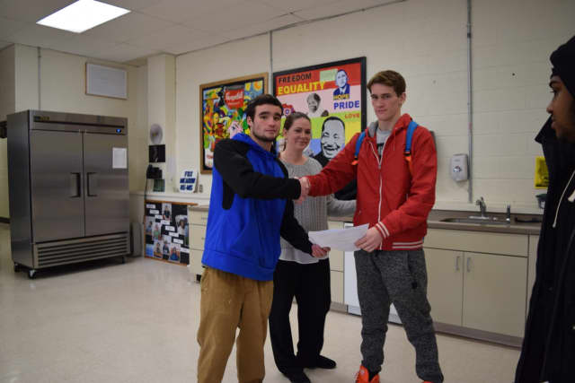 Fox Meadow senior Daniel Box (left) presents an award to fellow senior John Rodak (right) as Principal Nicole Murphy looks on. Fox Meadow recognized 36 students Friday for academic achievement and attendance.