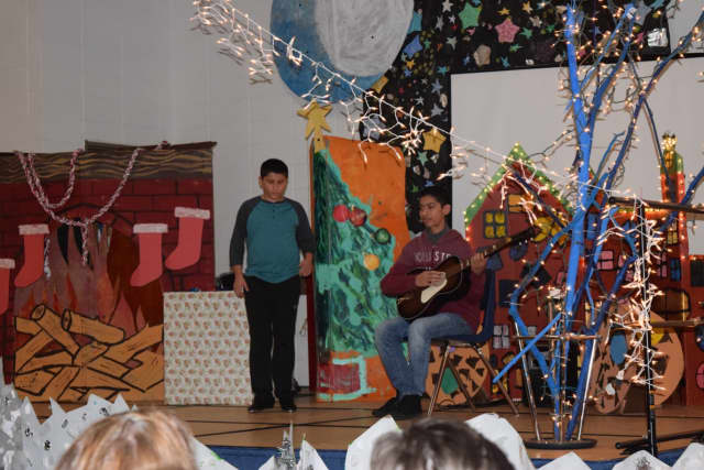 Evan Cardillo tap dances while Brandon Isocoa plays guitar during the Pines Bridge and Walden Schools Holiday Spectacular on Friday, Dec. 23.