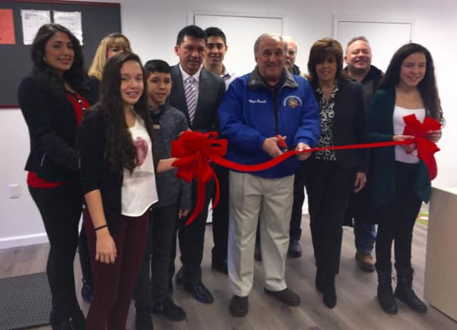 North Arlington Mayor Joseph Bianchi cutting the ribbon, flanked by Zobeida and Germanico Santana, and their triplets in the first row.