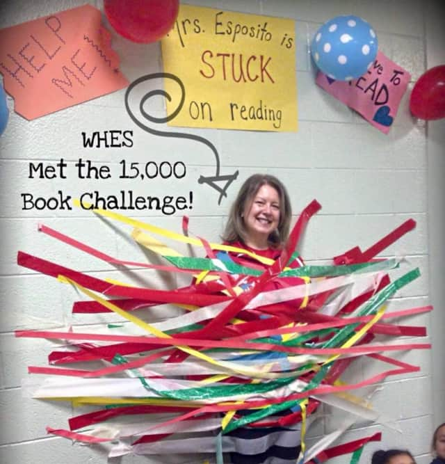 """Students at West Haverstraw Elementary School met Mary Esposito's reading challenge. As a reward for their hard work, the children got to tape Esposito to the wall because she was """"stuck"""" on reading."""