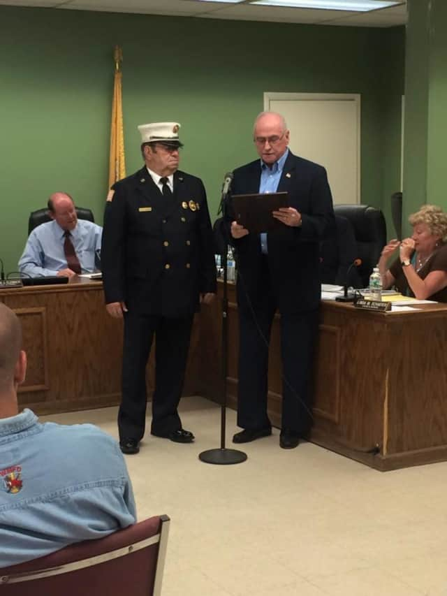 Ringwood Mayor Walter Davison, at right, honors longtime firefighter Dave Everson.