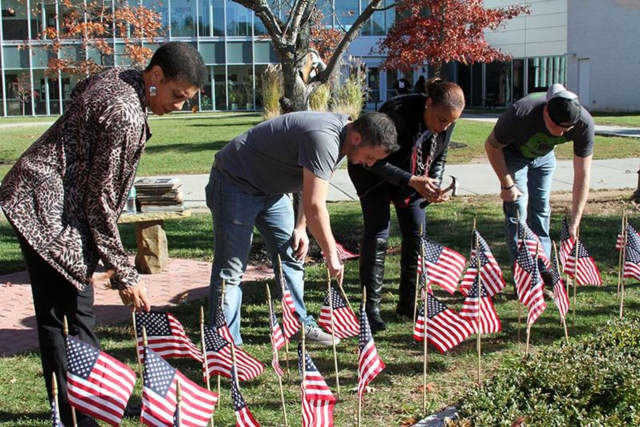 Maureen Brown, of student development, U.S. Army Spc. Corey Greene, Elizabeth Solages, of admissions, and Army Serviceman Jason Hellman ready the Rockland Community College campus for Veteran's Day.