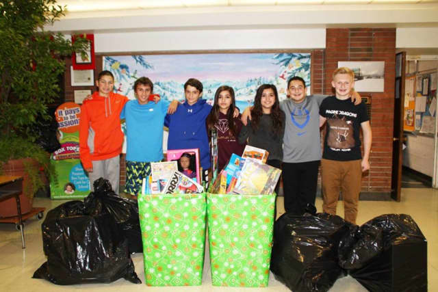 Pleasantville Middle School student council members pose with the proceeds from the toy drive they organized for the Fraternity of Notre Dame, which works with needy children in Harlem.