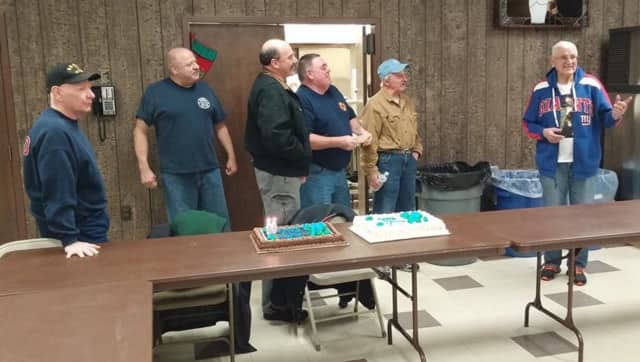 Pompton Lakes firefighters celebrate a milestone for member Albert Backus, at right.