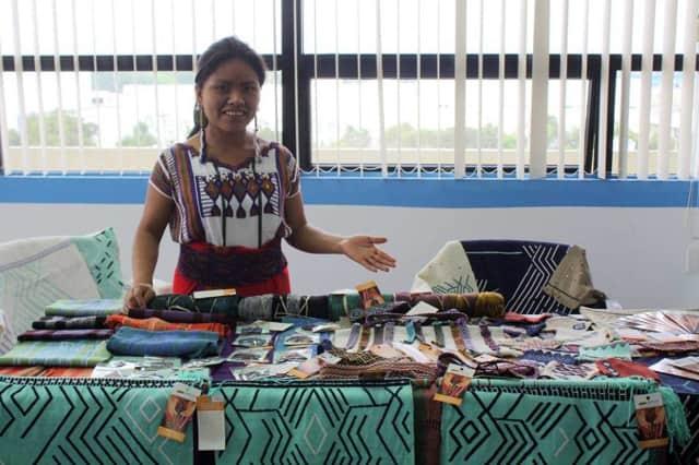 Limitless Horizons Ixil's Artisan Program leader Cecilia shows off a small sampling of products handmade in Chajul at a Guatemalan artisan fair.