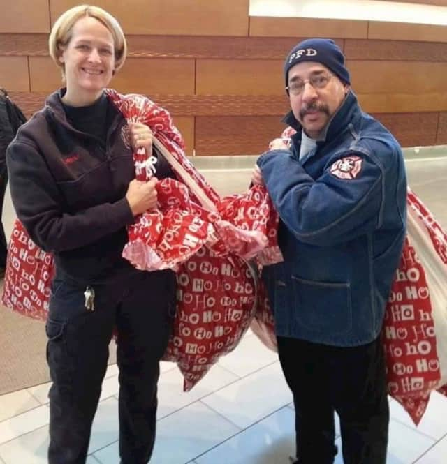 Paterson firefighter Beth Fournier and Luis Vega deliver stuffed animals to patients in the ER on Christmas Eve.