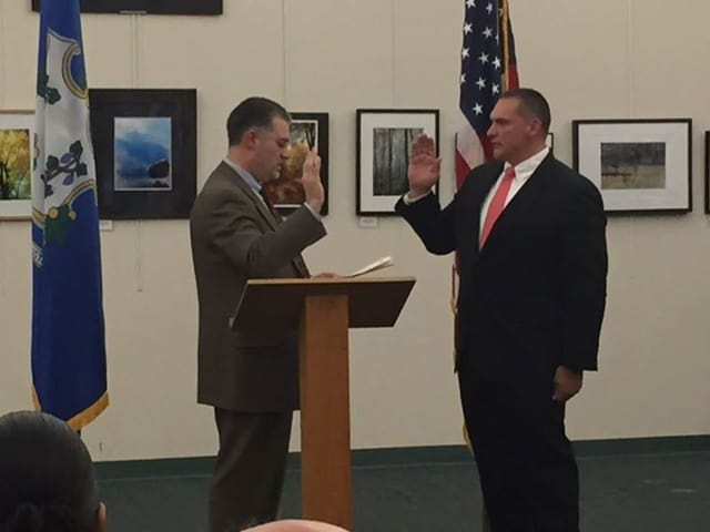 Chairman of the Police Commission, Richard Colangelo (left) administers the oath to Officer Arthur Belile, who is joining the Easton Police Department