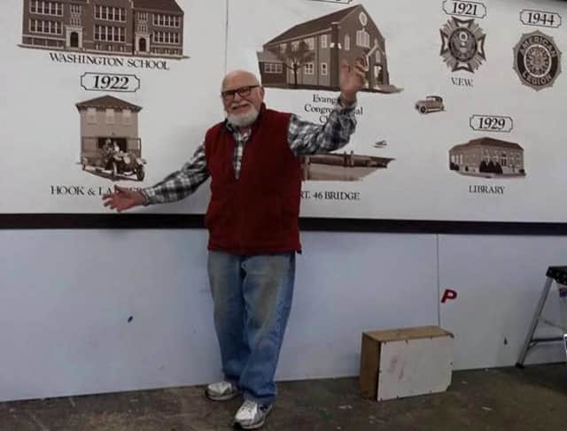 Bill Riedel, surrounded by Little Ferry history as part of his mural.
