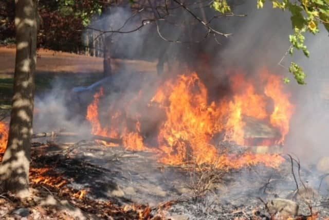 A firefighter pulled an unconscious person from a burning vehicle at a cemetery.