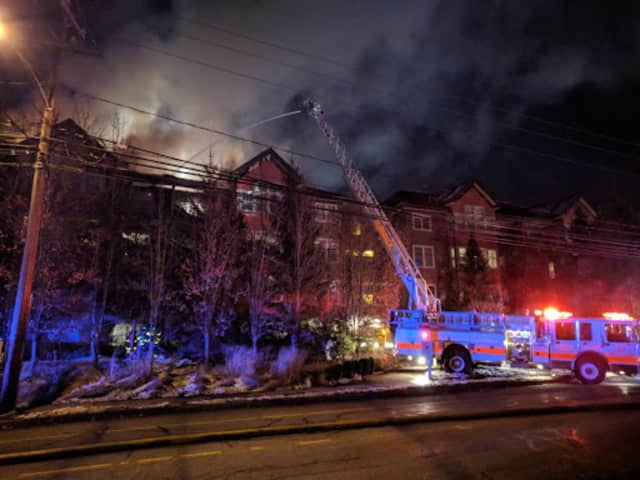Fire crews attack the blaze from above in the condo building on Richards Avenue in Norwalk on Monday evening.