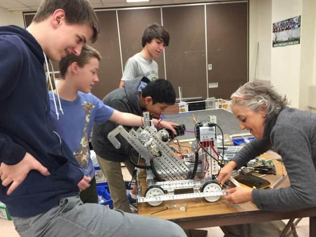 Mamaroneck High School Principal Elizabeth Clain helps the teens with their robot.