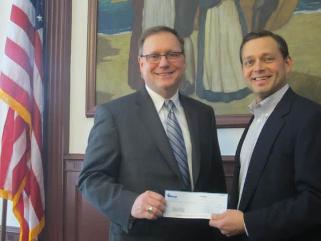 ENCON CEO Bill Valus presents a check for $1,600 to the Town of Stratford's open space fund.