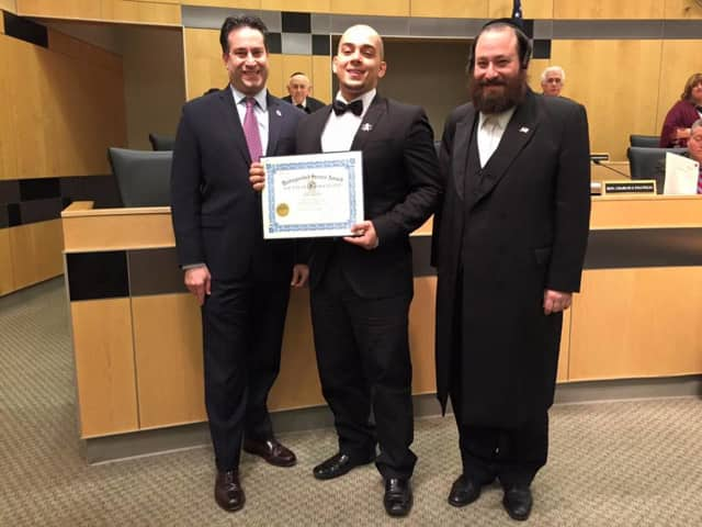 Rockland County Legislators Alden H. Wolfe, left, and Aron B. Wieder, right, present the Board's Distinguished Service Award to Joey Resto, center.
