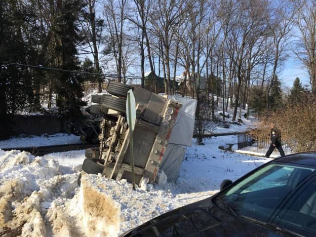 A tractor-trailer rolls over in the snow on Nashville Road in Bethel on Monday.