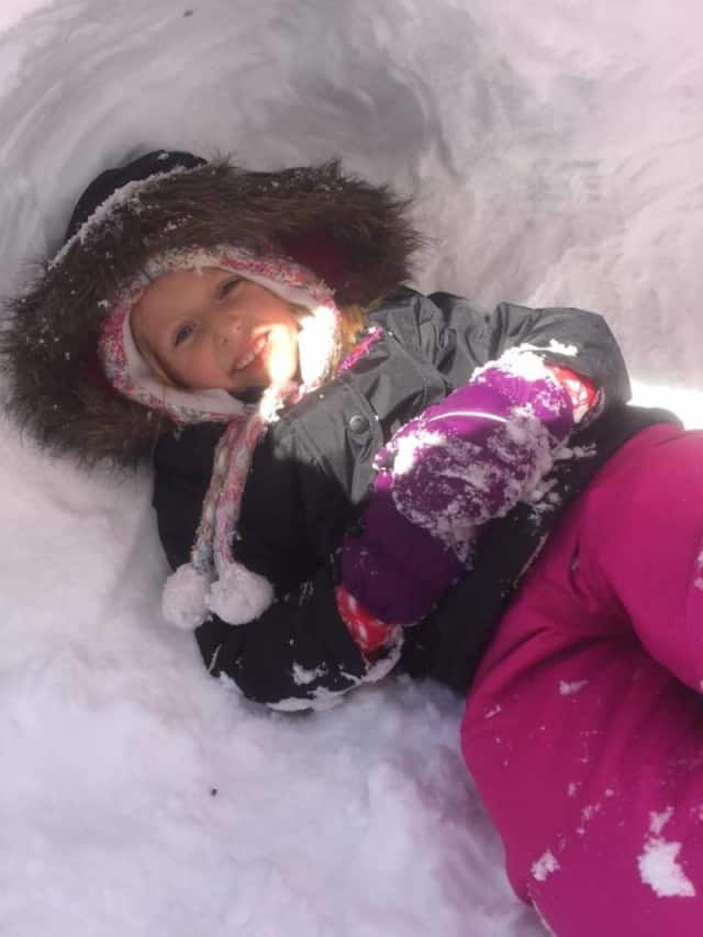 Sophia, 5, hangs out in a snow fort.