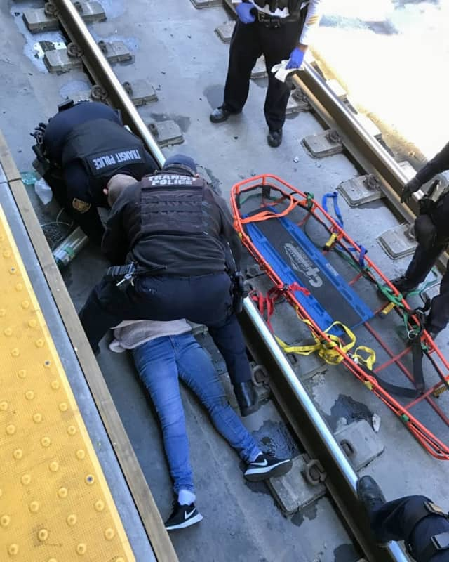 New Jersey Transit Police Officers rushed to save a woman suffering a seizure on railroad tracks at Newark Penn Station.