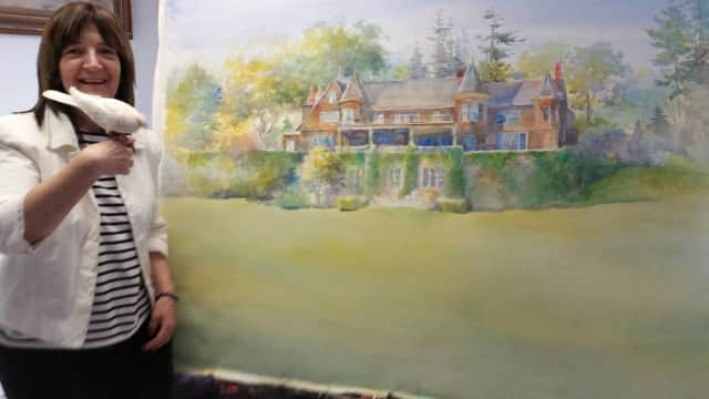 Theresa Troise Heidel with her painting of Oradell's Blauvelt Mansion.