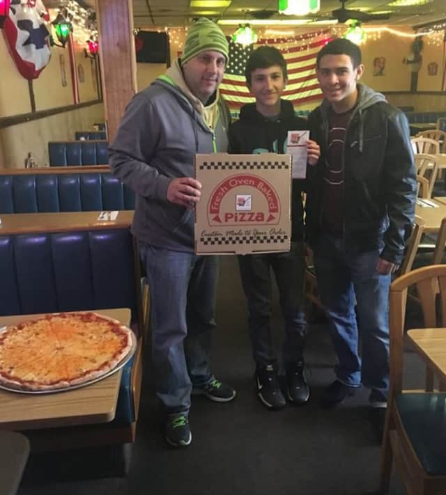 Garfield EPIC members help put stickers on pizza boxes at Barcelona's.