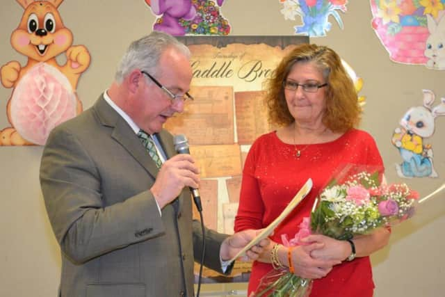 JoAnn Brendel holds her flowers after being honored by Saddle Brook Mayor Robert White at the township's Women's History Month event.