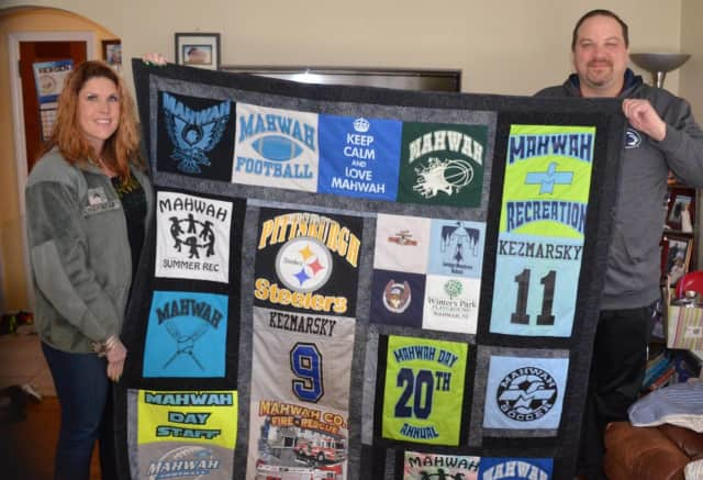Tammy Marcus, at left, and Ben Kezmarsky hold up a Mahwah-themed quilt.