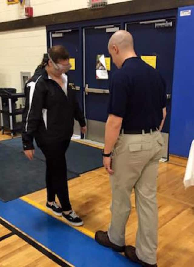 Brookfield Police Officer Jason Fiege shows a student the dangers of impaired driving at the wellness festival at Brookfield High on Tuesday.