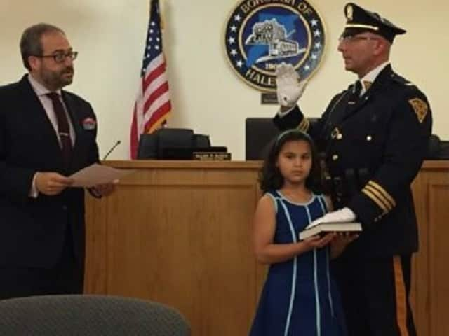 New Haledon Deputy Police Chief Angelo Daniele, with his niece holding the Bible, is sworn in by Mayor Domenick Stampone.