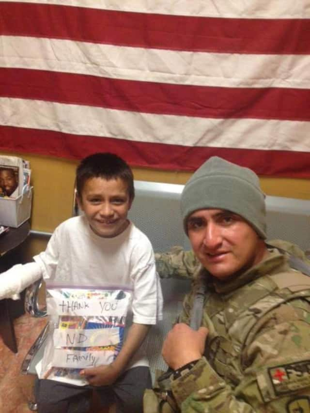 Fernando Moreno-Rivas, who was killed in a wrong-way crash on Route 8, presents gifts to an Afghanistan boy in 2012. Fernando Moreno-Rivas was an Army medic.