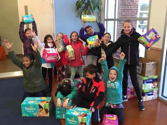 Children at the Village School Monessori hold up diapers their school collected for a CAFS diaper drive in May.