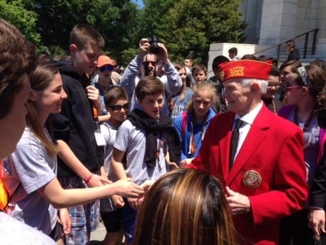 World War II veteran Mr. Fricks surrounded by students.