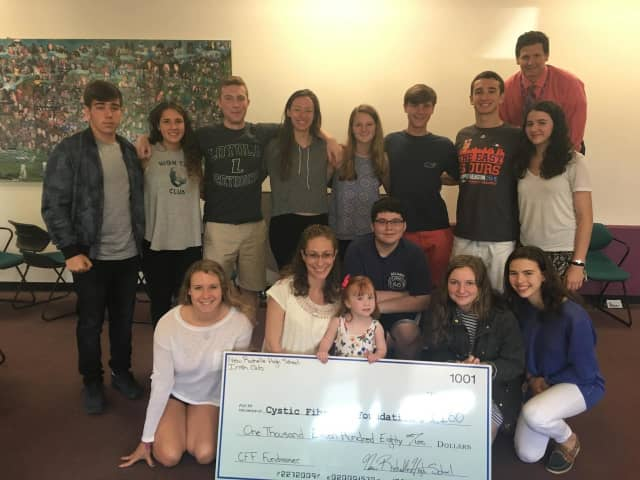 The Irish Club pose with their fundraising check.