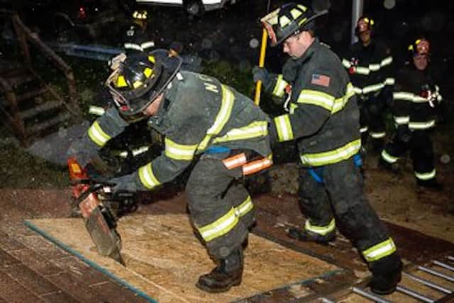 The New City Fire Department firefighters use power saw during the drill.