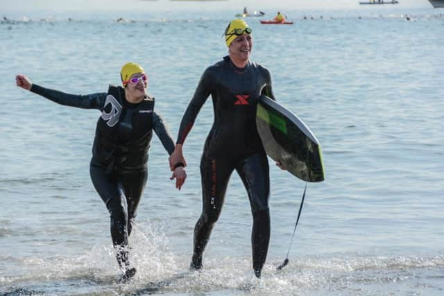 Chrissy Vita, left, and Terri Peri of Mahwah exit the water at the Cohasset Triathlon on Sunday.