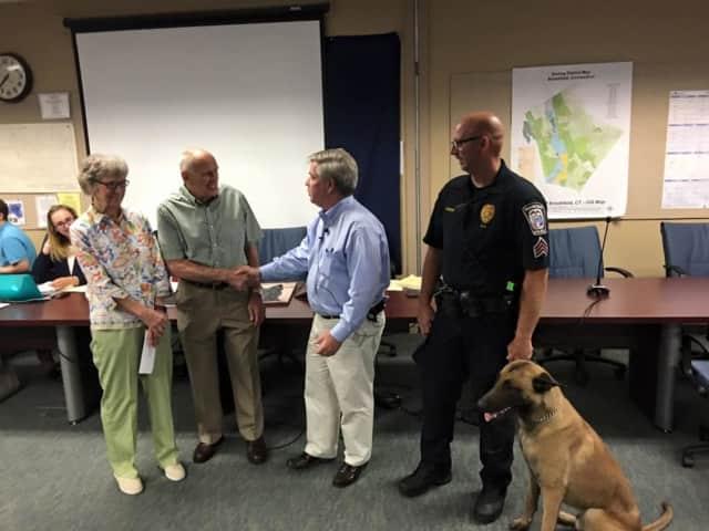 First Selectman Steve Dunn shakes hands with Warren Malkin as Ruth Malkin (left) meets Police Sgt. Jeff Osuch and Argo.