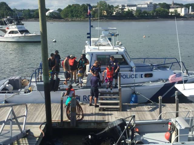 A member of the New Rochelle Police Department Harbor Unit helped rescue two people stranded in the water after their boat hit a rock.