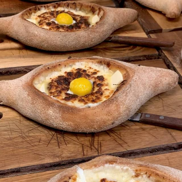 One of Badagenoi's favorite bread, Khachapuri is a dish that's like an open-faced cheese boat with an egg on top.