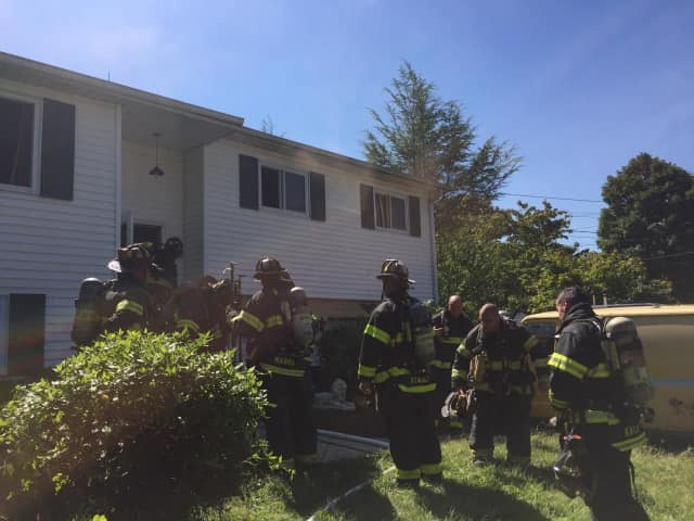 Firefighters responding as smoke comes from the second floor.