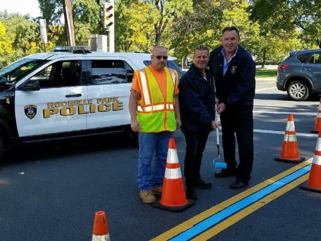 Rochelle Park Police Chief Robert Flannelly and Police Commissioner Jay Kovalcik joined DPW laborer Roy Spraguer in paint the township's thin blue line.