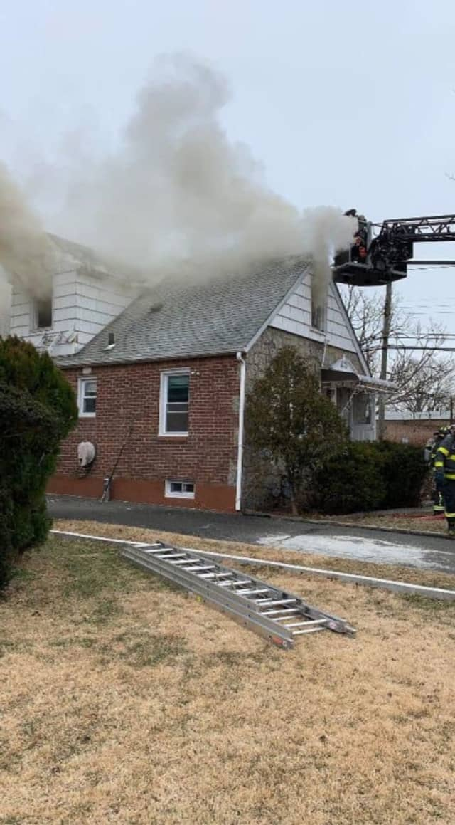 Three people were rescued by a police officer from a burning home in New Hyde Park.
