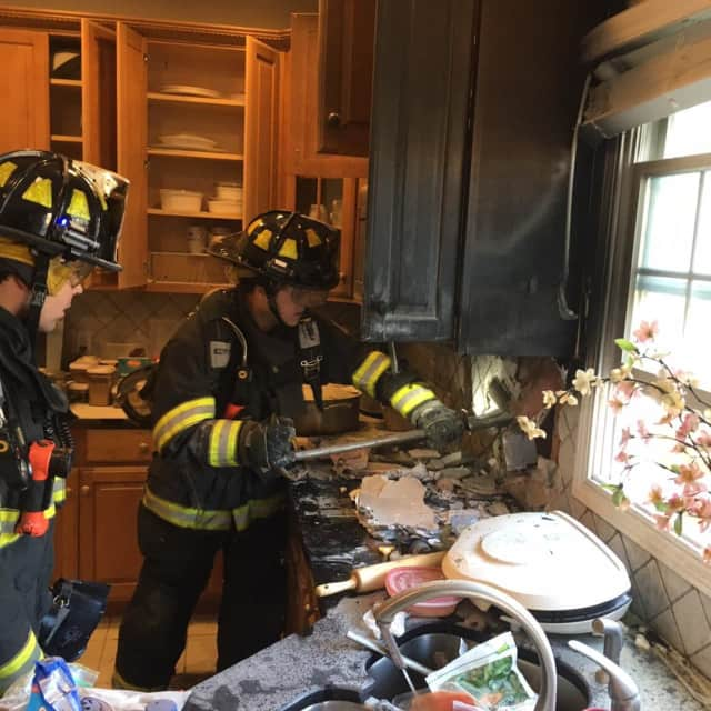 Firefighters from the Monroe Volunteer Fire Department put out a fire in a kitchen.