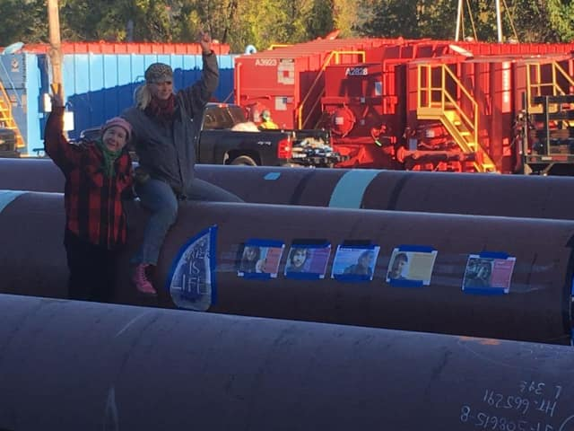 Two protesters sit atop one of the pipes Monday being used to construct the Algonquin Pipeline project.