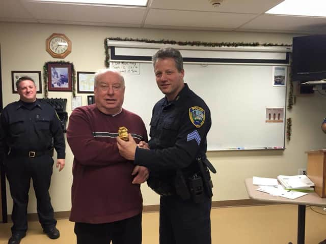 Ossining police Sgt. Vinnie DiLeo receives his 'retired' badge on his last day on the job from recently-retired Chief Burton .