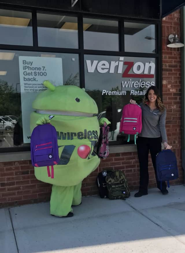 Brewster Verizon Wireless Zone store manager, Katie Kaslyn, pictured with backpack giveaways